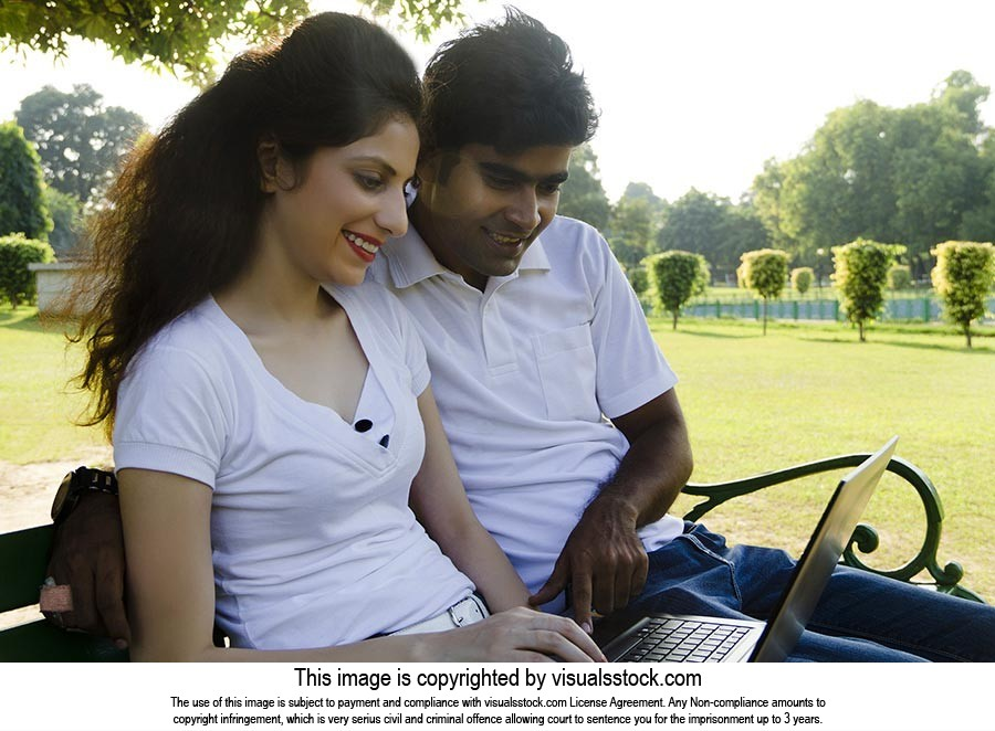 couple sitting park bench using laptop Chatting