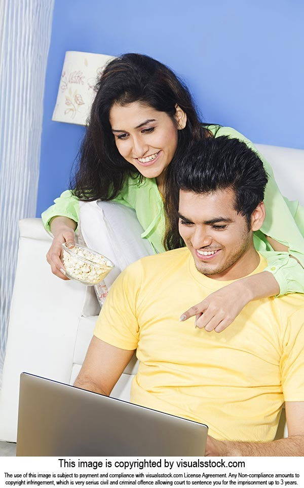 Couple Sitting home Laptop Chatting Finger Pointin