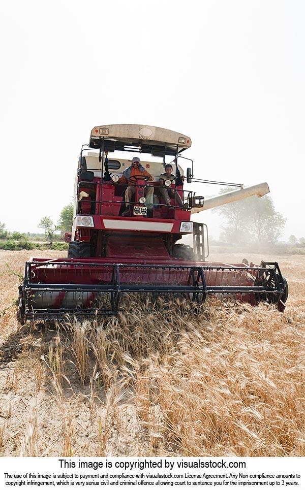 farmers Combine Machine harvesting wheat in fields