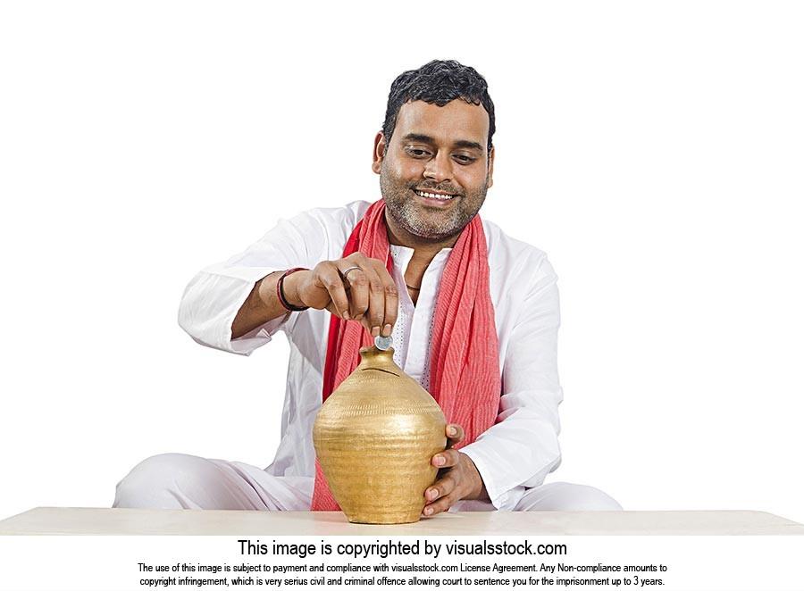 Indian Rural Man Putting Coin Piggybank