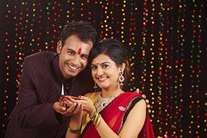 Couple Celebrating Diwali Lighting Diya