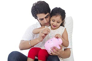 Indian father and Little daughter saving money pig