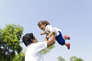 Father tossing up his little daughter in the air I