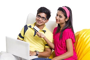 Teenager Couple Sitting Beanbag Laptop With Debit