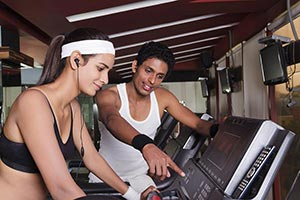 Man Assisting A Woman On A Treadmill Gym Exercise