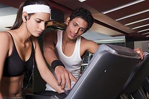 Trainer helping assisting a woman on a treadmill W