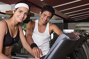 Male Trainer Assisting Woman Cross-Trainer Machine