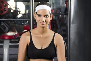 Young woman practicing yoga exercise Gym Smiling