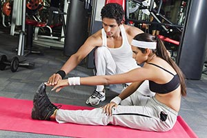 Male Trainer Helping Woman With His Exercises Gym