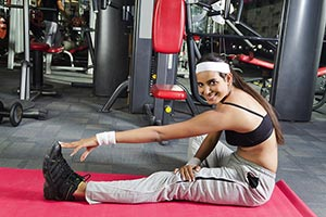 Indian Fitness Woman doing Exercise stretching leg