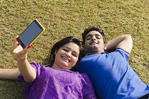 Indian Couple Taking Selfie Lying Park