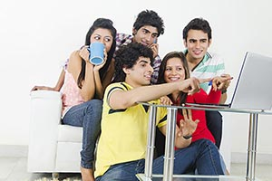 Indian Young friends sitting Sofa Laptop Pointing
