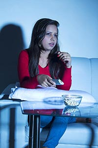 Young Woman Sitting Sofa Watching TV Eating Popcor
