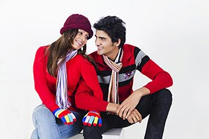 Indian Young Couple Winter Clothes sitting togethe