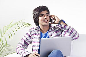 Teenager Boy at home Laptop Talking Phone