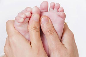 newborn baby holding Feet s Mother Caring