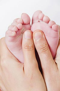 Mother holding newborns baby foot