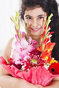 Little Girl smiling holding bouquet flowers