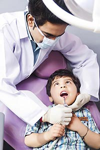 Male dentist examining a Kid patient at clinic