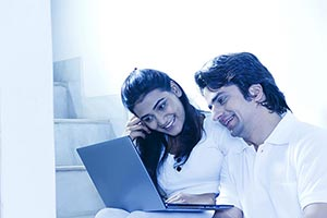 Couple Indian Smiling using laptop together Chatti