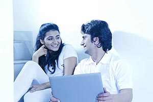 Smiling Couple Using Laptop Chatting At Home