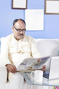 1 Indian Man Sitting On Sofa Reading Newspaper At