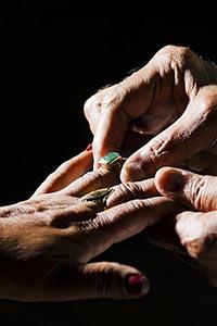 Close Up Senior Couple Hand Inserting Anniversary
