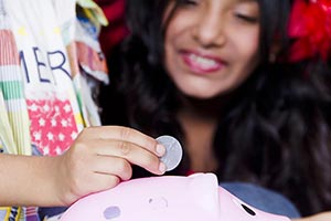 Kids Putting Coins Piggy Bank