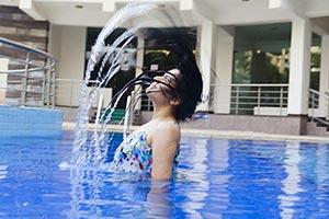 Woman Splashing Water Hair Swimming Pool