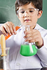 Young little Boy scientist doing research with che