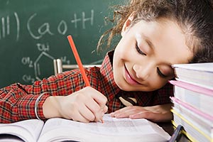 Smart Child school girl with pencil and books writ
