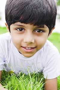 Indian Kid Boy Lying Grass Park Relaxing Smiling