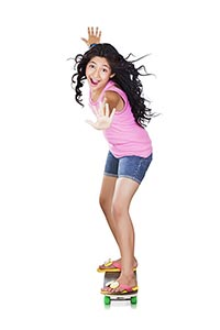 Cheerful teenage girl riding a skateboard is balan