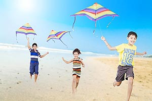 Happy Children flying a colorful kite running in s