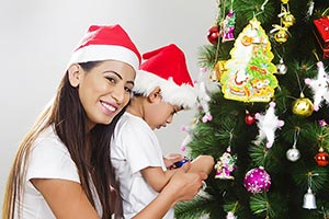 Boy And Mother Decorating Christmas Tree Smiling