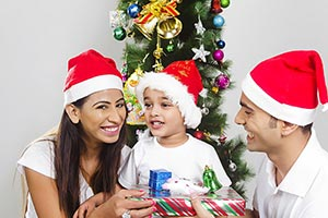 Indian Smiling parents giving Christmas Gift son