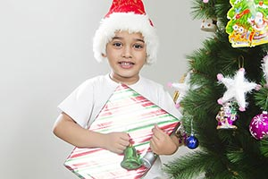 little boy celebrates Christmas Tree presents gift