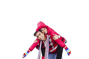 Happy couple winter clothes playing piggyback Enjo