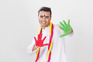 Indian Man showing colourful palm celebrating holi