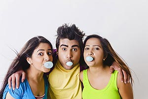 Happy Fun Young friends blowing chewing gum bubble