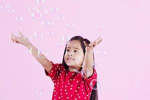 Little Girl Catching Soap Bubbles
