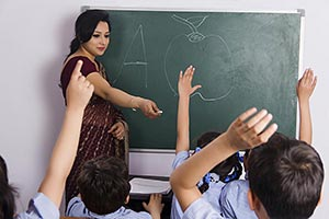 Female Teacher Teaching Children Classroom