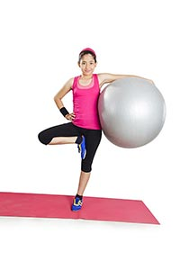 Young Girl Standing On One Leg Fitness Ball