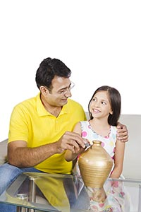 Father Daughter Putting Coin Piggybank