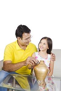 Father Daughter Putting Coin Piggybank