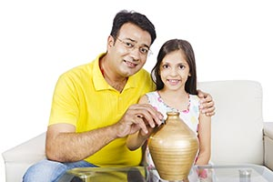 Father Daughter Inserting Coin Piggybank