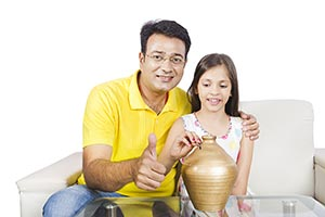 Father Daughter Inserting Coin Piggybank Thumbsup