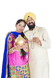 Indian Sikh Couple Saving Money Piggybank