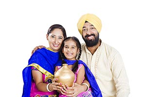 Indain Sikh Family Saving Money Piggybank�
