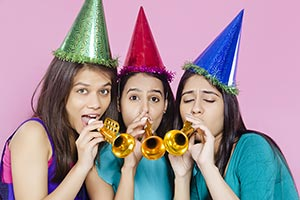 Teenage Girls Blowing Party Horn